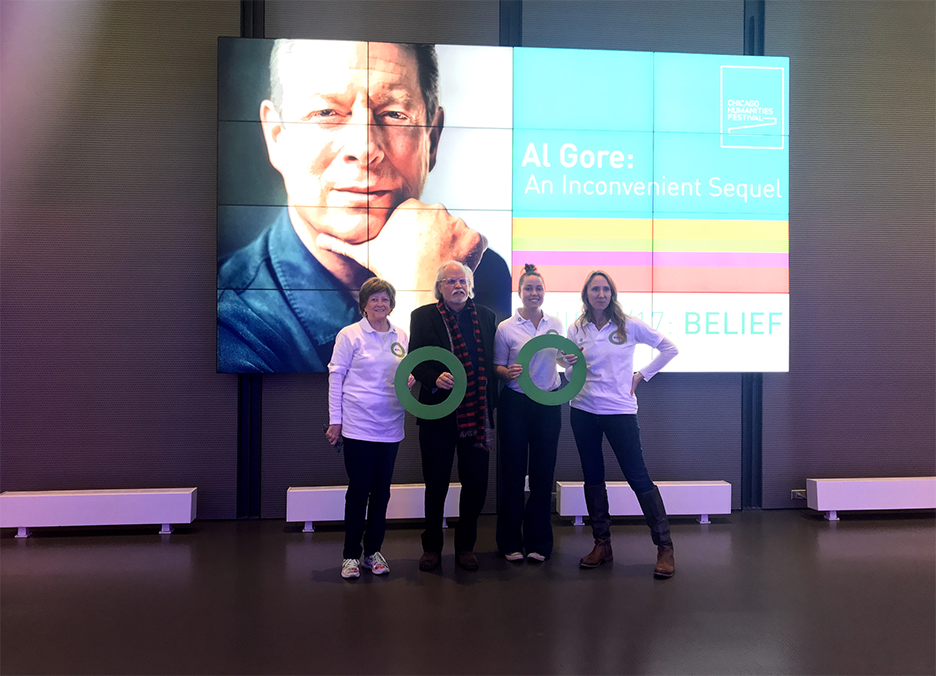 four climate leaders holding green rings standing in front of a sign showing Al Gore