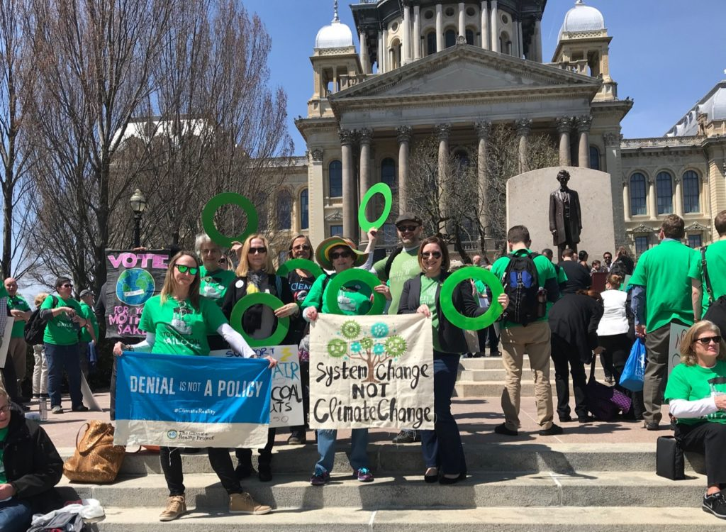 climate reality leaders in outside the Capital Building in Springfield, IL holding signs and green rings