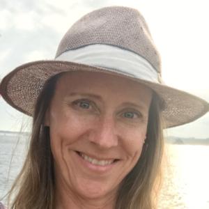 Jennifer Linton outside by Lake Michigan wearing a hat with a white ribbon