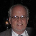 Howard Mock wearing glasses, suit and tie
