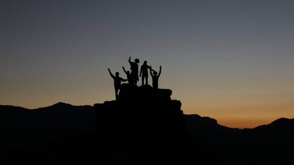 sunset photo of a mountain with a small group of people in silhouette